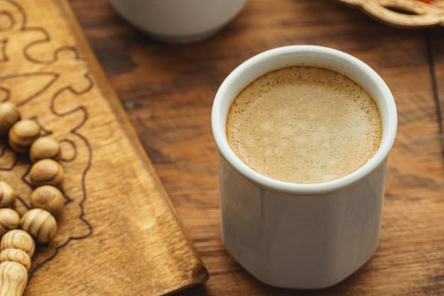 東洋の宗教的なビーズはコーヒーと木製のテーブルにクローズアップ