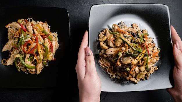 동양 레스토랑 요리 제공. 닭고기와 야채 식사와 함께 두 접시를 들고 여자