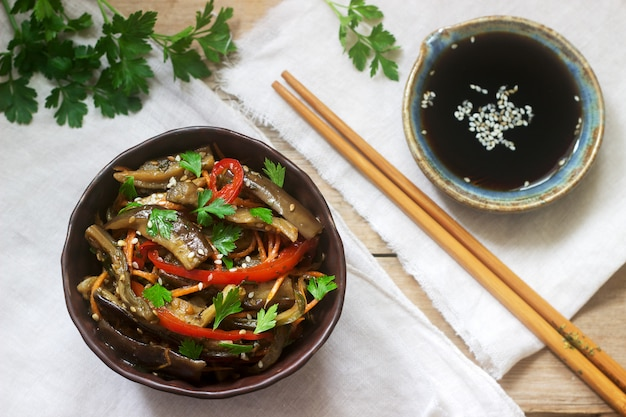 Oriental style vegetable salad with eggplant, soy sauce and chopsticks on a wooden table. rustic style.