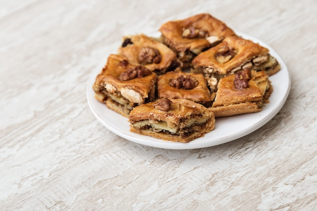 Oriental sweets baklava with honey and nut on white plate. tasty oriental dessert on wooden background with copy space