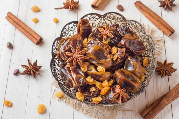 Oriental sweets, dried fruit dates and raisins, cinnamon and star anise in a plate.