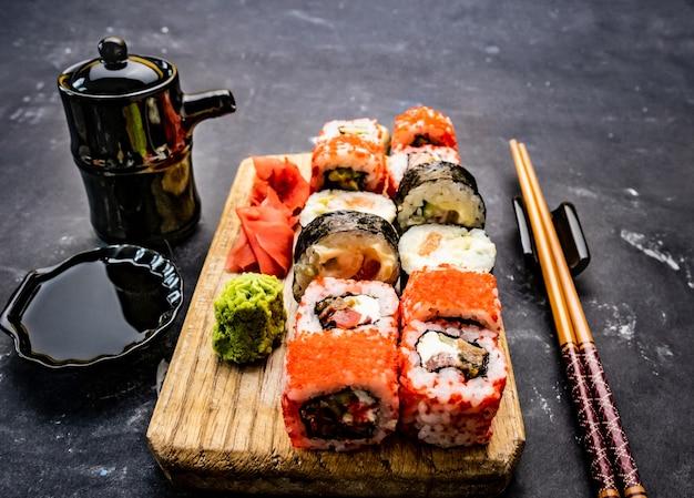 Традиционный восточный набор суши-маки, подаваемый на деревянных таблетках с соевым соусом из палочки для еды и зеленым васабом ...