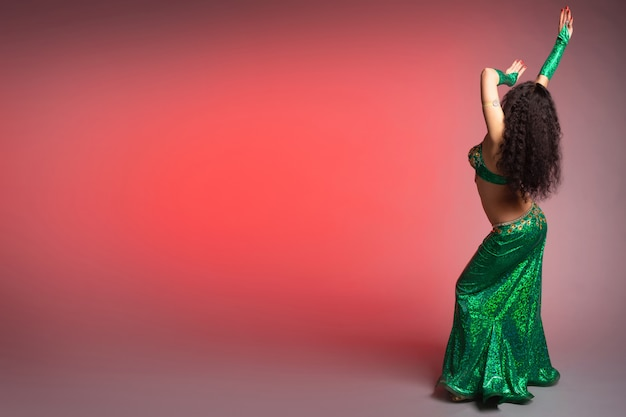 Oriental woman belly dancer in a beautiful green costume