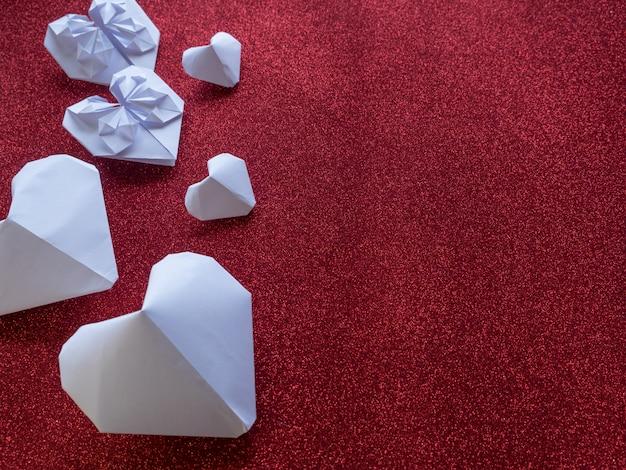 Orig ami紙のハートは、赤いハートのギフトリボンとバレンタインデーのシンボルを形成します。テキストまたはデザイン用のコピースペース