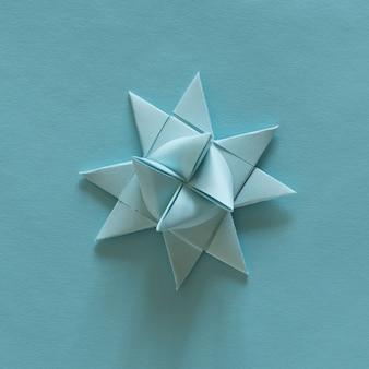 Оригами 3d звезды, голубые, на голубом фоне. концепция украшения. орнамент. современное бумажное искусство и ремесло.