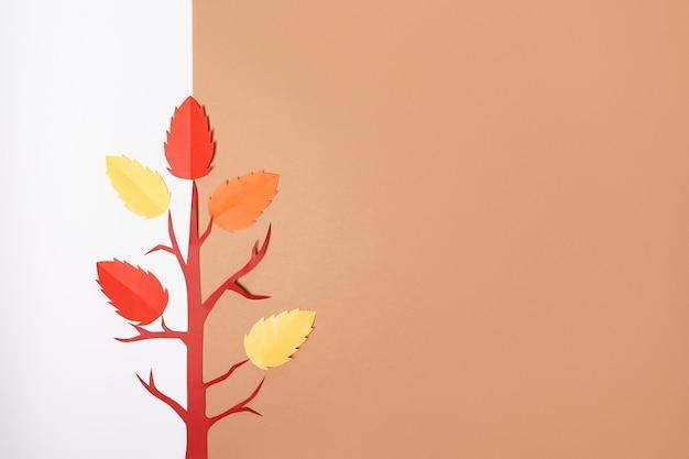 흰색과 갈색 배경에 떨어지는 잎이 있는 종이접기 가을 종이 나무, 복사 공간
