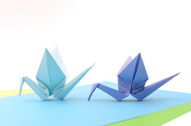 Оригами птицы над голубой бумагой. детские бумажные статьи.