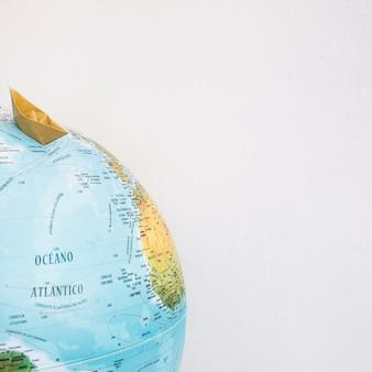 Origami boat on globe