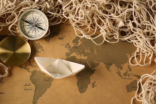 ヴィンテージ世界地図上の折り紙ボート。旅行のコンセプト