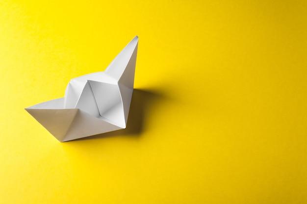Оригами лодка из бумаги на желтой поверхности
