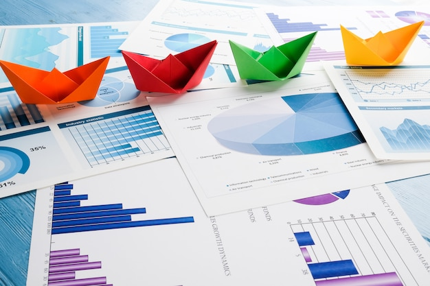 Origami boats on business chart on a wooden table