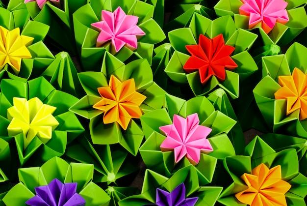 さまざまな花の折り紙の束が背景をクローズアップ