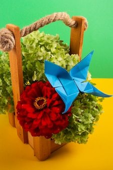 Origami butterfly on a green bush in a basket on a colored background beautiful bouquet studio close shot with red rose