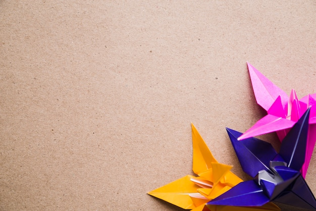 Origami colorful paper flowers on cardboard texture background