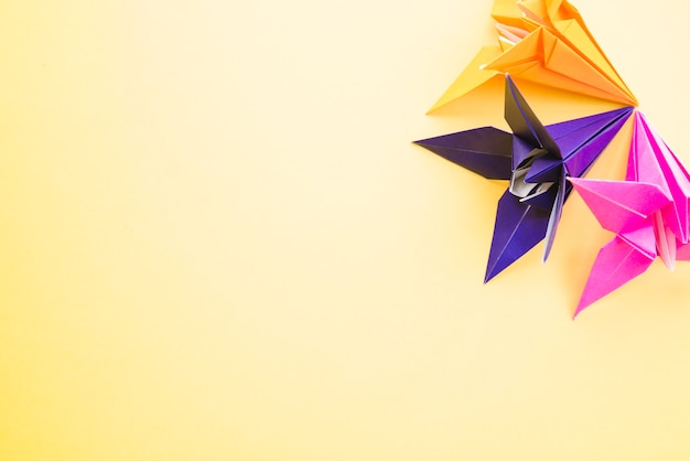 Origami colorful paper flowers on yellow background