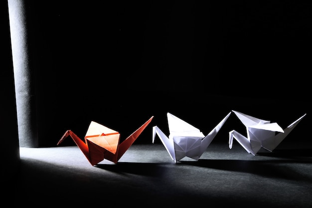 Оригами журавликов на темноте со светом