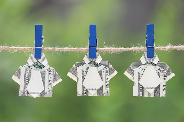 Origami dollar shirt on hanging nature green background