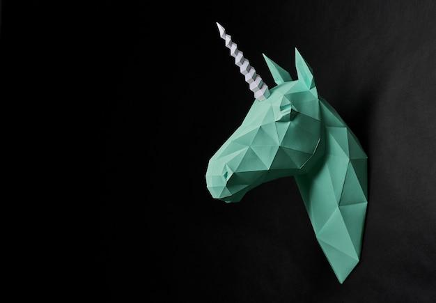 Оригами тусклый зеленый голова единорога висит на черной стене.