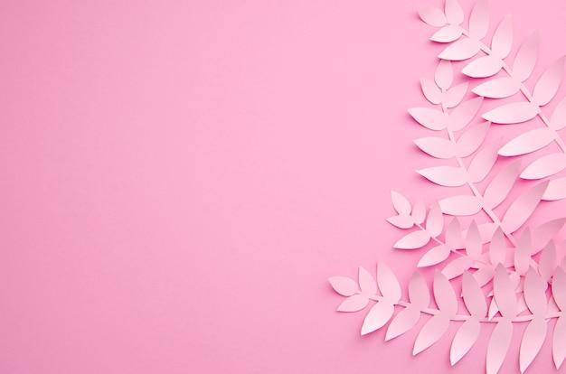 ピンクの背景の折り紙のエキゾチックな紙の植物