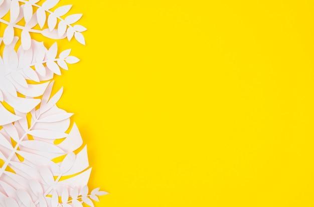 黄色の背景に折り紙のエキゾチックな紙の植物