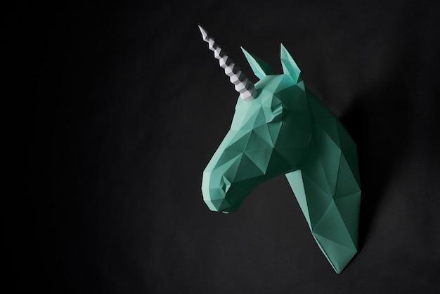 Голова оригами зеленого единорога висит на черной стене.