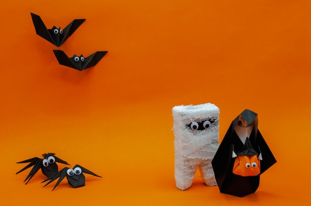 The origami halloween background of the nun holding pumpkin head jack-o-lantern and mummy run away from bats and spiders