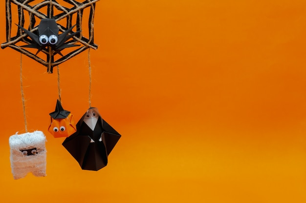 The origami halloween background of pumpkin head jack-o-lantern, mummy and nun hanging on spider cobweb on orange.