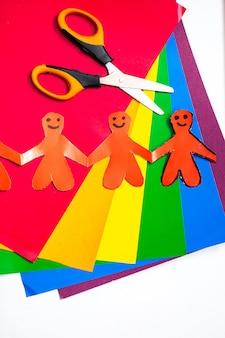 色とりどりの紙の背景に手をつないでいる男性の形の折り紙