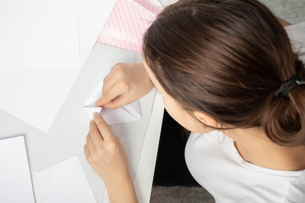 Origami is the ancient art of folding paper. female hands make a figure