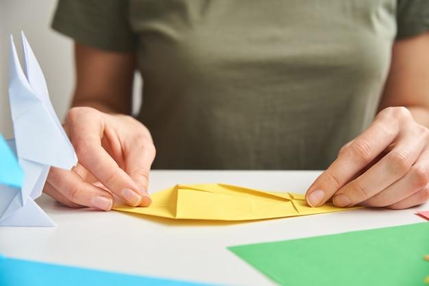 종이 접기 수업. 여자 색 종이에서 종이 접기 부활절 토끼 만들기