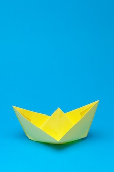 Origami paper boat on blue
