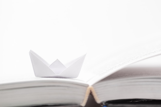 Origami paper boat on a book