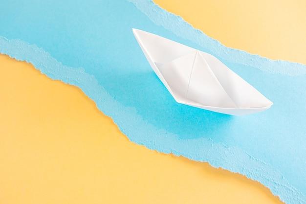 カラフルな破れた紙片に折り紙紙の船