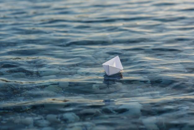 折り紙の紙の船が水面に出航
