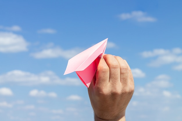 Origami paper plane in young male hand on blue cloudy sky surface