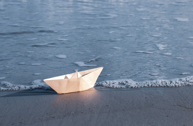Origami paper sailboat embarking on a journey to the sea