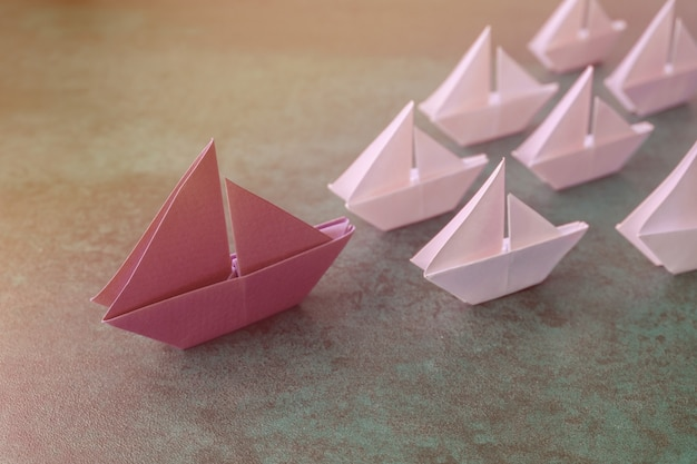 Origami paper sailboats, female woman leadership business concept