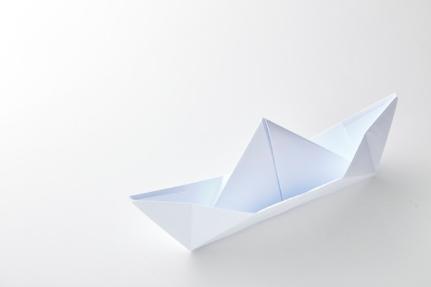 Origami paper ship on white