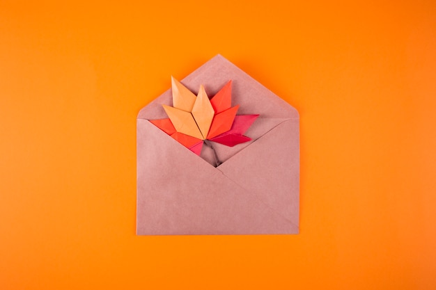 Origami papercraft autumn concept fallen leaves letter in an envelope on a plain background handmade craft art close up