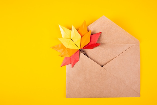 Origami papercraft autumn concept fallen leaves letter in an envelope on a plain background handmade crafted art