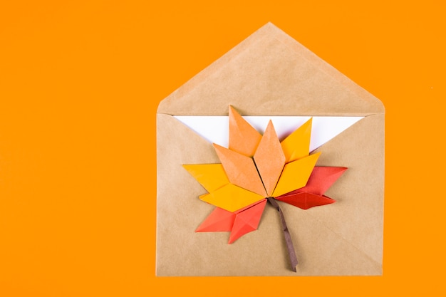 Origami papercraft autumn concept fallen leaves letter in an envelope on a plain surface craft art