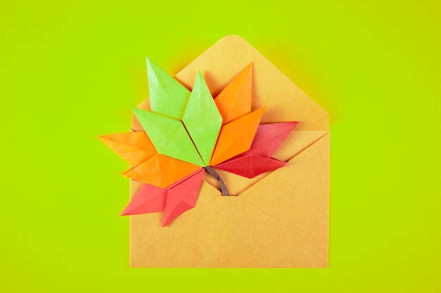 Origami papercraft autumn concept fallen leaves letter in an envelope on a yellow background handmade craft art