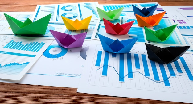 Origami ships on business charts.