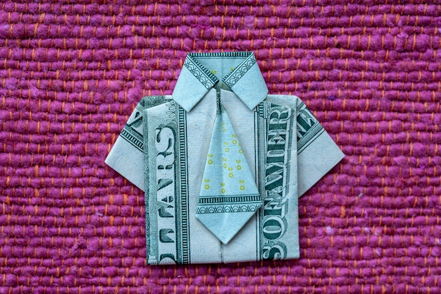 Origami shirt made of dollar banknote on red fabric background. close up. dollar bill t-shirt