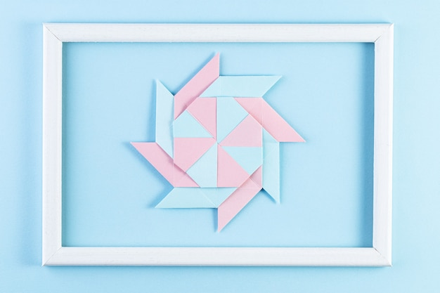 Origami star. made with square sheets of paper and white wood frame.