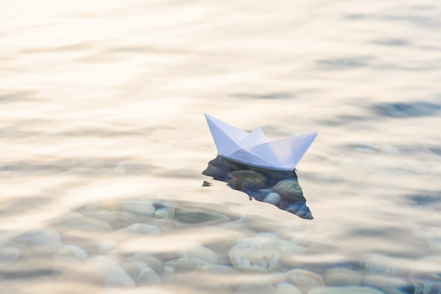 Origami white paper boat on blue deep water.
