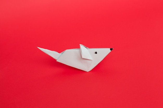 Origami white paper mouse on red background.