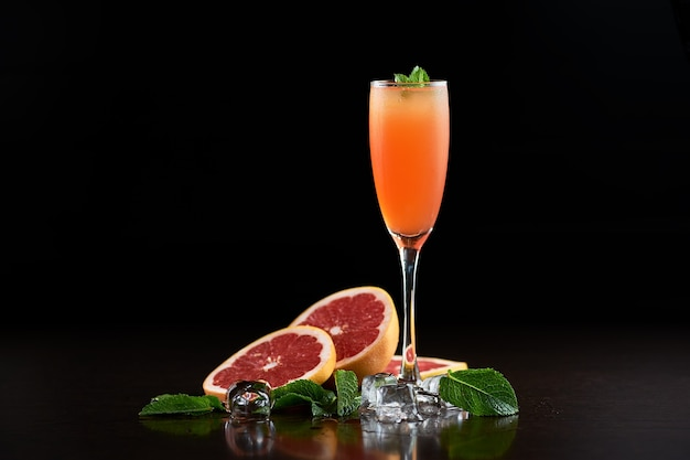 Original composition of tall cocktail glass with cold summer refreshing orange juicy drink, slices of grapefruit, fresh green mint leaves and transparent ice cubes on deep black copy space background.