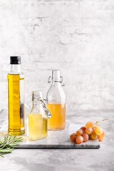 白いレンガの壁のテーブルに対して大理石のテーブルにさまざまな酢が入ったオリジナルのガラス瓶。スペースをコピーします。垂直。