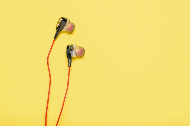 Original headphones for smartphone with red cable on yellow.
